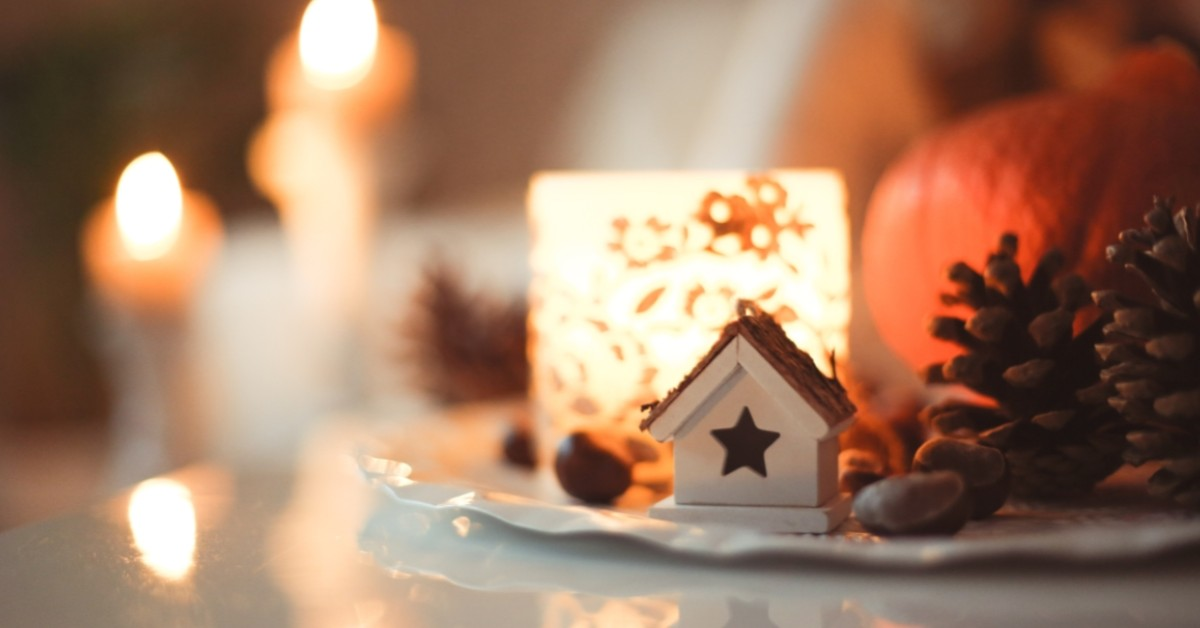 Image of a small figurine of a house surrounded by holiday lights and pine cones.