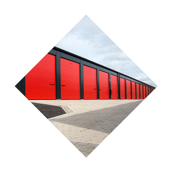 A long line of red garage doors in a storage facility.