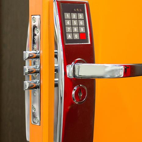 A keypad door lock on a yellow door.