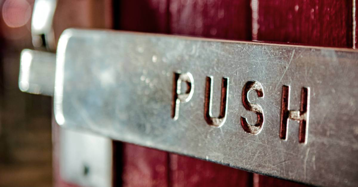 A close-up image of a push bar on a commercial door.