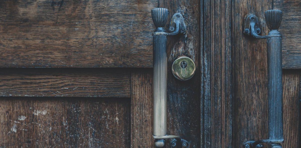 An image of dark wood doors with handles.