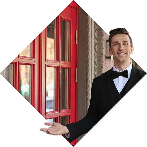 An image of a young, well-dressed man motioning to red double doors.