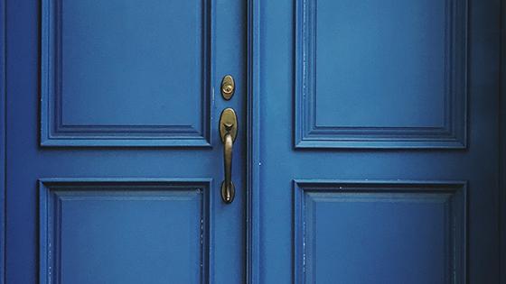 Beautiful paneled doors with a brass door knob and lock.