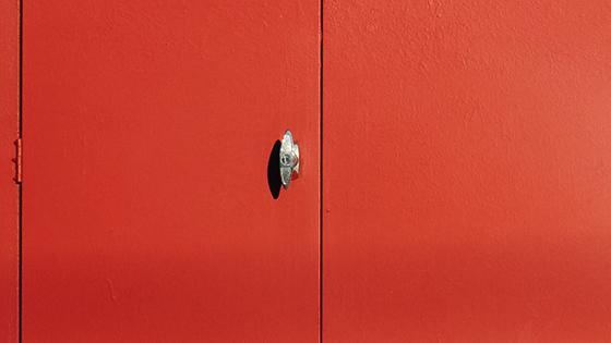 A red commercial door with a metallic angular doorknob.