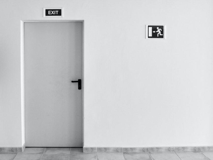 An image of a white commercial door against a white wall.