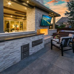 Covered outdoor living space with additional patio area and outdoor countertops by Compass Outdoor Design