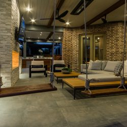 Patio design by Compass Outdoor Design feautres an outdoor fireplace, TV, living area, kitchen, and more!