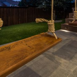 Patio design features timeless concrete tile and swings