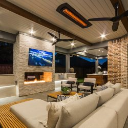Warm patio design by Compass Outdoor Design includes an outdoor fireplace, television, and furniture for the ultimate comfort.