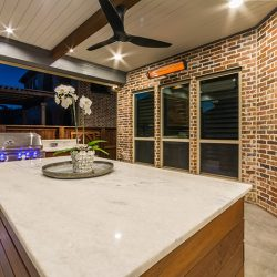 Outdoor kitchen in Dallas by Compass Outdoor Design includes a built-in grill, island, and more!