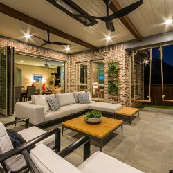 Inviting outdoor living space by Compass Outdoor Design includes seating, an outdoor fireplace, and swings!
