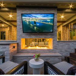 Outdoor living area design by Compass Outdoor Design includes two-sided outdoor fireplace, TV, hot tub, and more!