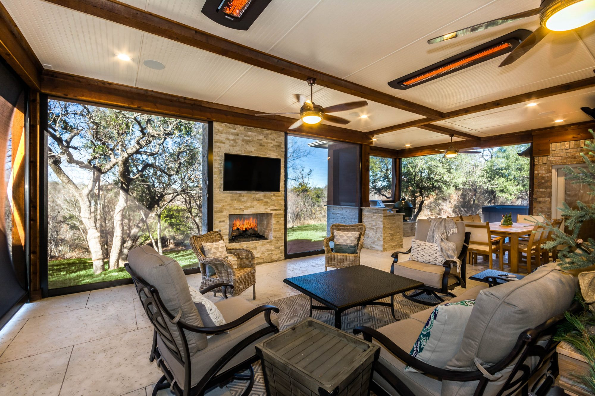 Outdoor living area in Dallas designed by Compass Outdoor Design includes an outdoor fireplace, television, seating area, and more!