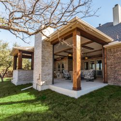 Covered living area with an outdoor fireplace built by Compass Outdoor Design in Dallas, TX