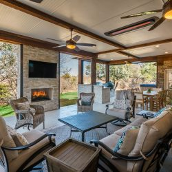 An outdoor fireplace, kitchen, and other features are included in this outdoor living space design done by COmpass Outdoor Design