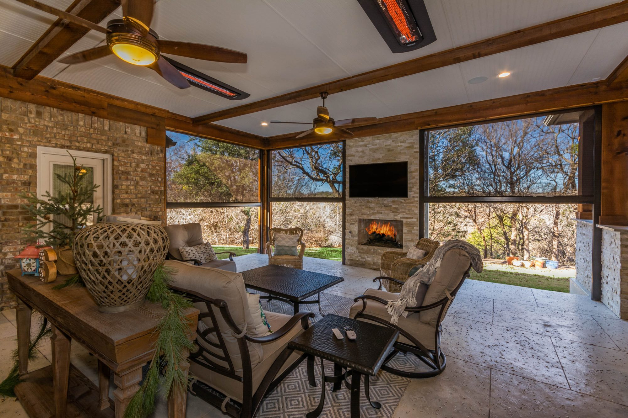 Enclosed outdoor living area with patio furniture near a outdoor fireplace designed and constructed by Compass Outdoor Design