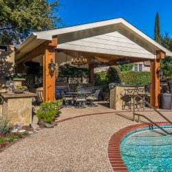 View of a covered patio in Dallas next to a swimming pool.