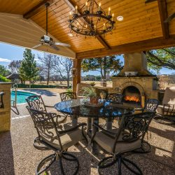 Spacious outdoor living space in Dallas with dining area, kitchen, and an outdoor fireplace included!