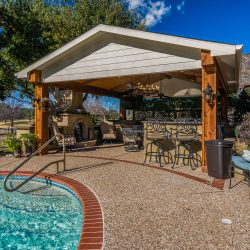 An outdoor living space in Texas located next to an inground swimming pool. Contact Compass Outdoor Design to begin designing your outdoor living space.