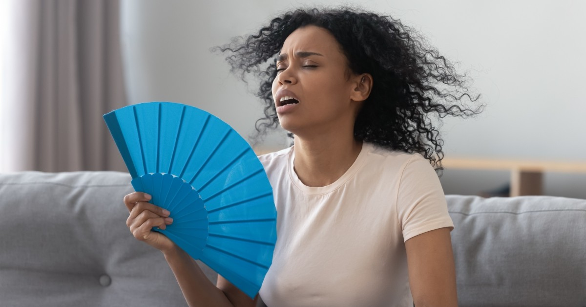 Image of a woman fanning herself to cool off.