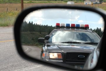image of car's side mirror with police car in reflection