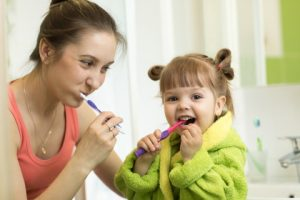 Photo of a mother and daughter brushing their teeth.