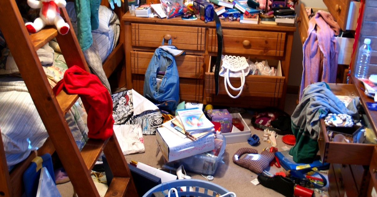Cluttered room with junk in drawers and on the floor.