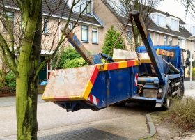 Blue truck delivers colourful waste container