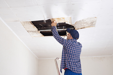 Man repairing a collapsed ceiling.