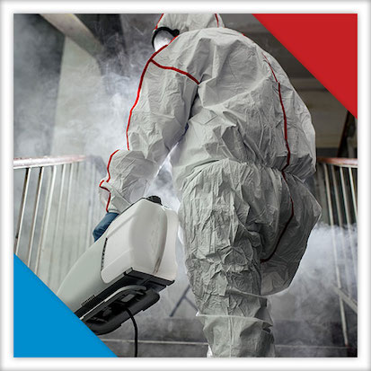 Image of a person in a suit spraying a disinfectant