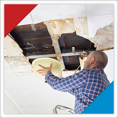 Image of a man inspecting a water leak in the ceiling