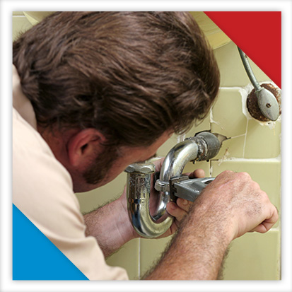 Image of a man trying to fix a leaky bathroom pipe