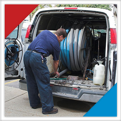 Image of a man from a professional water cleanup service getting a large hose out of his van