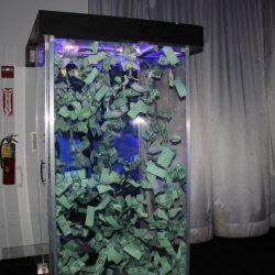 Active money machine blowing around dollars