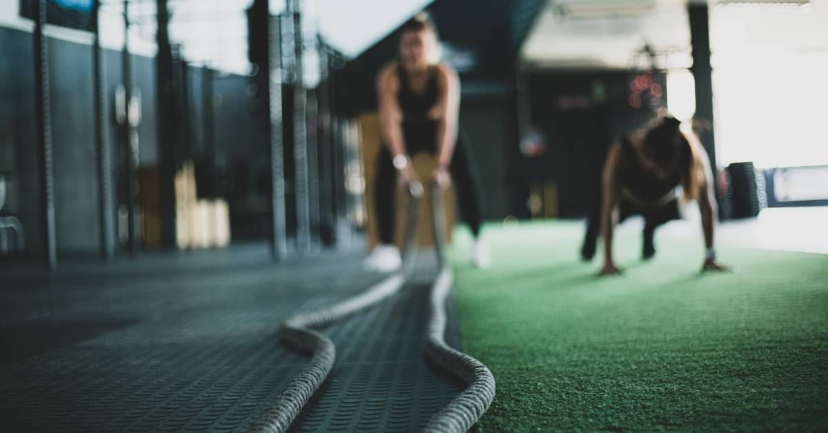"A woman bends over to grab exercise ""battle ropes"" in preparation for a workout."