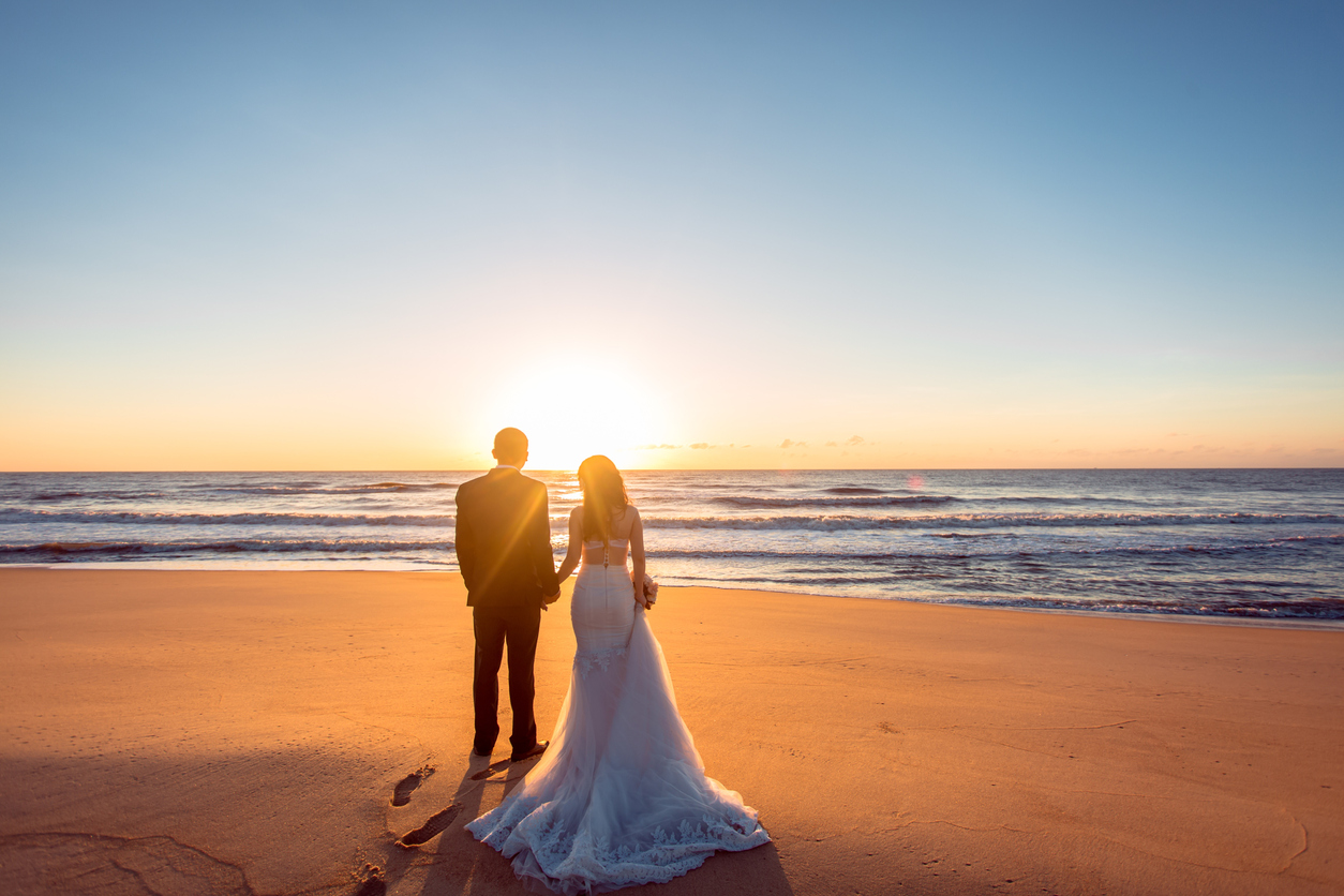 Newly weds standing on the beach at sunset