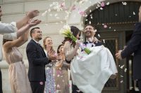Groom carrying bride while leaving from church