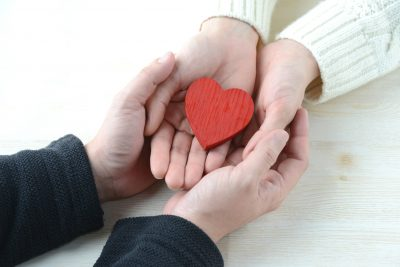 Red heart being held by couple in their hands