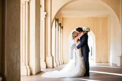 Bride and groom passionately kissing under arch for wedding photos