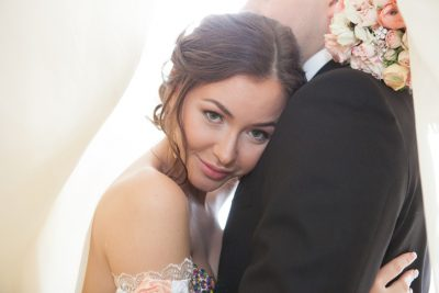 Bride leans on grooms shoulder and looks at the camera in a ballroom