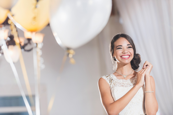 Portrait of a mixed race teenage girl wearing a white dress. She is ready for her birthday party. Balloons in the background as part of the quinceanera decoration package
