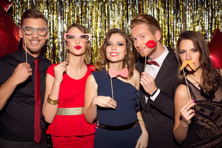 Young people wearing elegant clothes celebrating or having party in front of fringe curtain. They are holding photo booth fake props as moustaches, glasses and kiss lips and posing at camera.