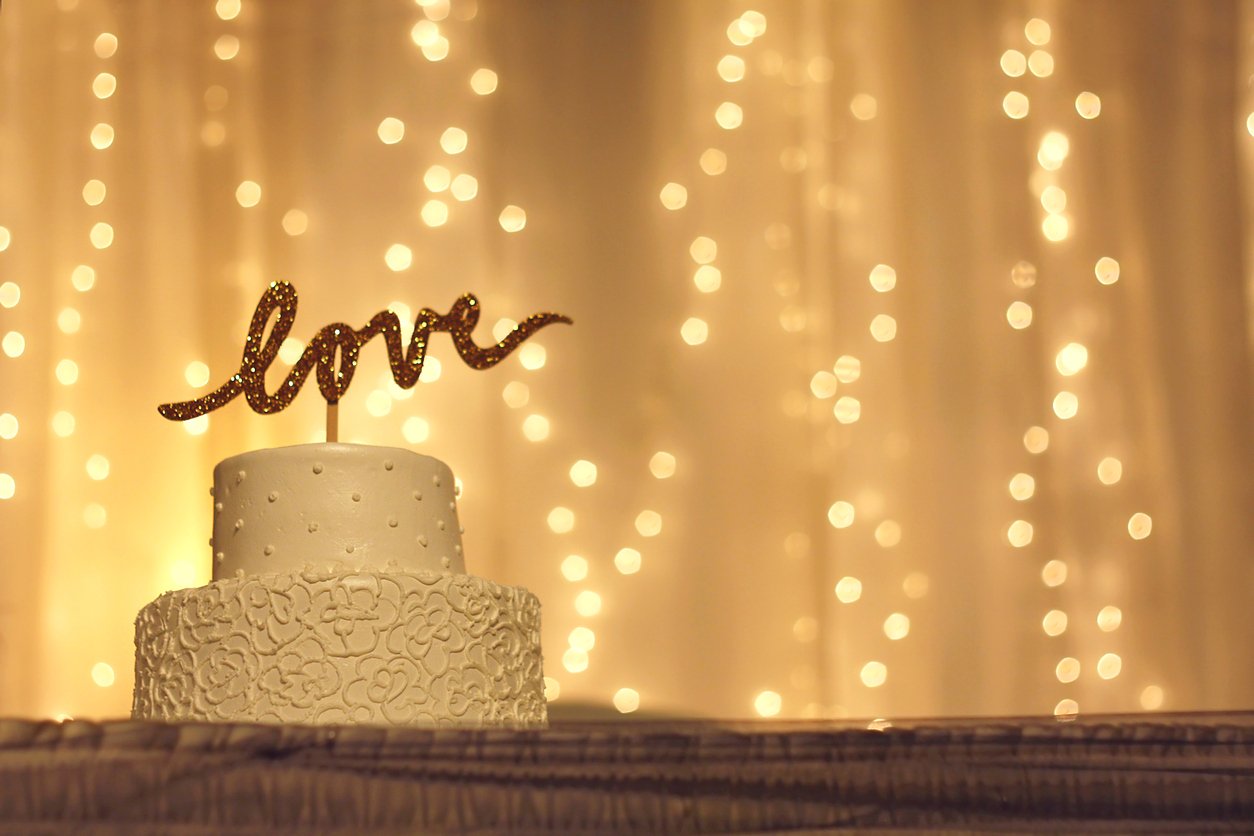 a simple white wedding cake with the word love written in sparkling gold letters on the top, with white twinkling lights and fabric in the background