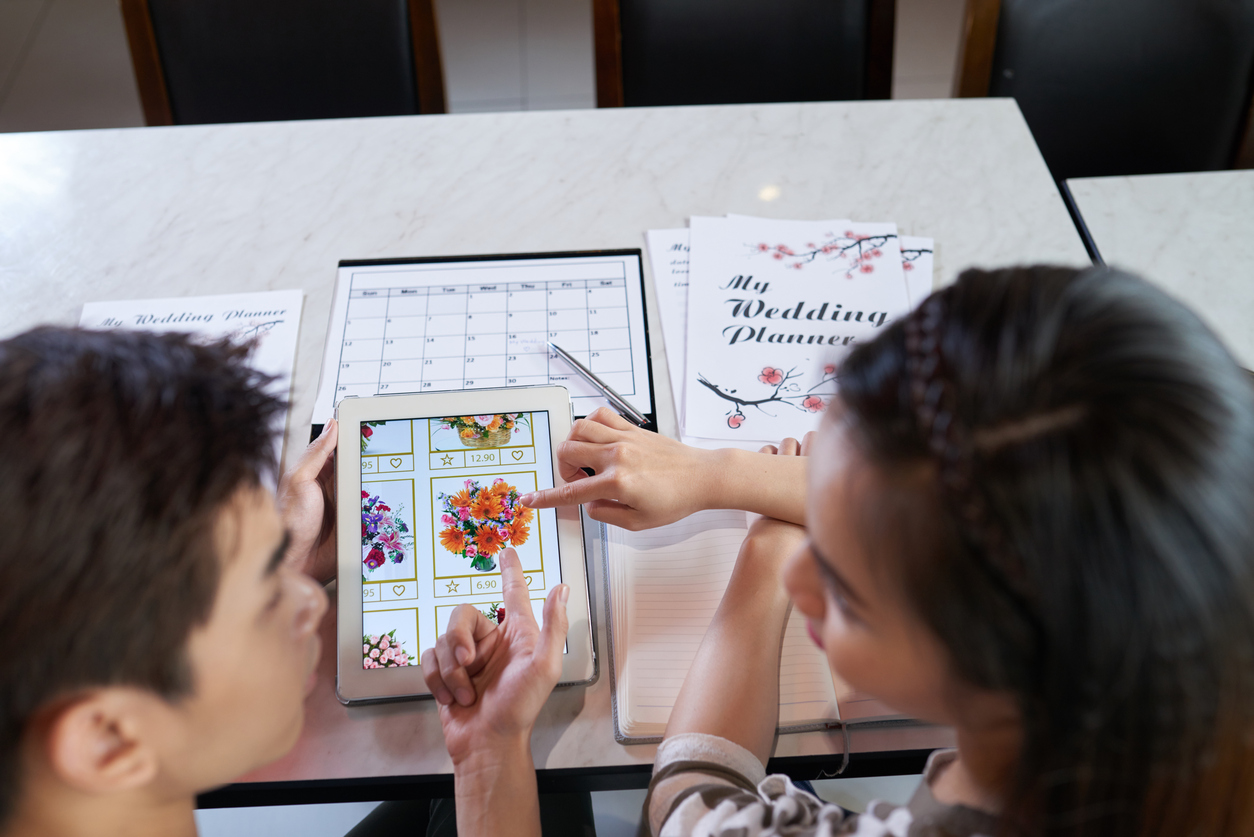 Over shoulder view of young Asian couple choosing bridal bouquet with help of digital tablet while planning wedding day at home