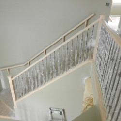 Unfinished wooden railing with metal spindles.