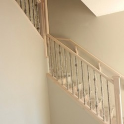 Corner shot of stair railing with wood and metal structure.