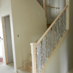 Stairs and landing with new wood railing and metal spindles.