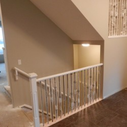 Stair railing and landing banister in wood and metal.