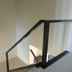 Metal rail casing for glass railing, looking downstairs.