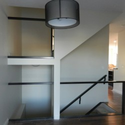 Two-part staircase with metal railing for glass inserts.